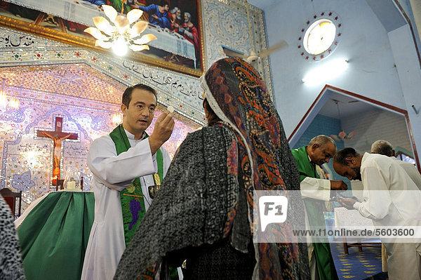 Gottesdienst  verschleierte Frau empfängt die Kommunion  Pfarrkirche St. John  christliche Gemeinde Youhanabad  Lahore  Punjab  Pakistan  Asien