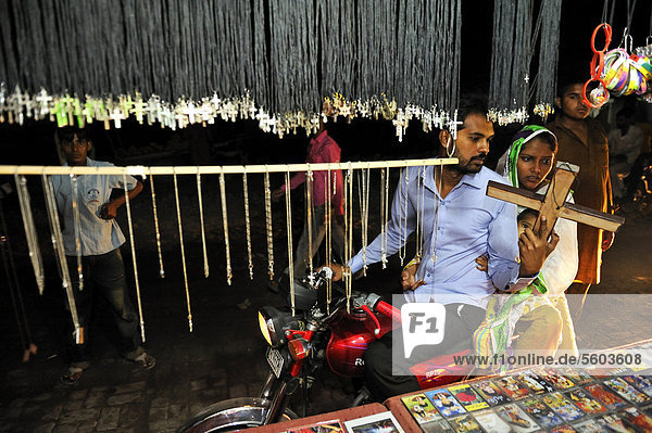 Young family on a motorbike purchasing a wooden crucifix at a stall offering Christian products  Christian quarter of Youhanabad  Lahore  Punjab  Pakistan  Asia