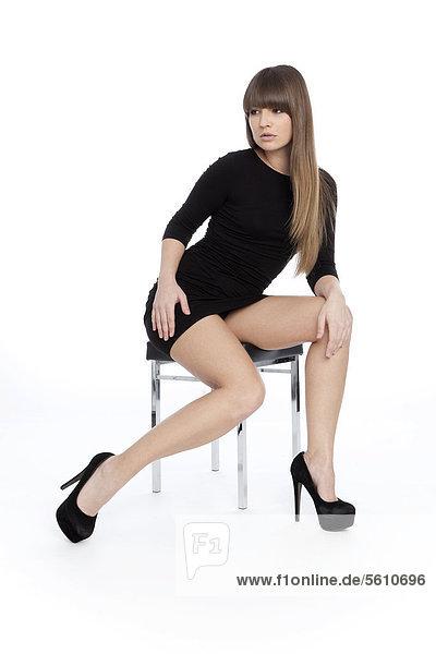 Junge Frau posiert selbstbewusst in kurzem schwarzem Kleid mit High Heels