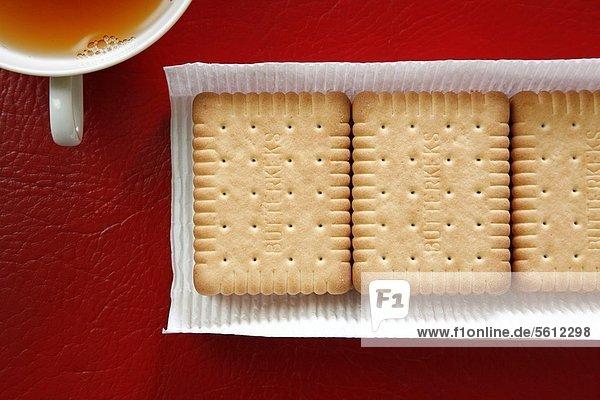 Packung mit Butterkeksen und Tasse Tee