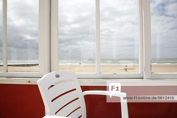 Strand hinter Stuhl und Fensterscheibe