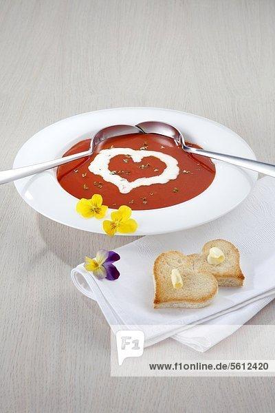 Tomatensuppe mit herzförmigem Toast und Blüten Tomatensuppe mit herzförmigem Toast und Blüten