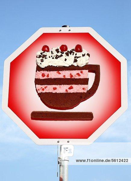 Sahnetorte in Form einer Kaffeetasse auf einem Stopschild Sahnetorte in Form einer Kaffeetasse auf einem Stopschild