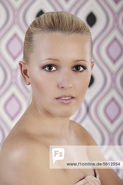 Junge Frau  Portrait vor Retro-Tapete