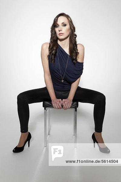 Junge Frau posiert in blauem Oberteil  schwarzen Leggins und High Heels