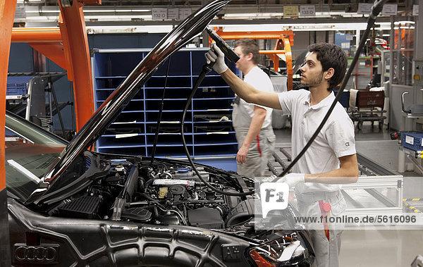 An Audi employee installing hooks on an Audi A4 Sedan  assembly line  Audi plant  Ingolstadt  Bavaria  Germany  Europe