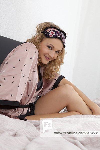 Junge Frau mit Bademantel im Bett