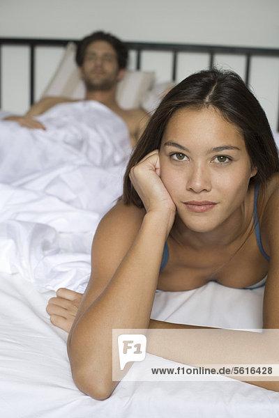 Junge Frau auf dem Bett liegend  Freund im Hintergrund