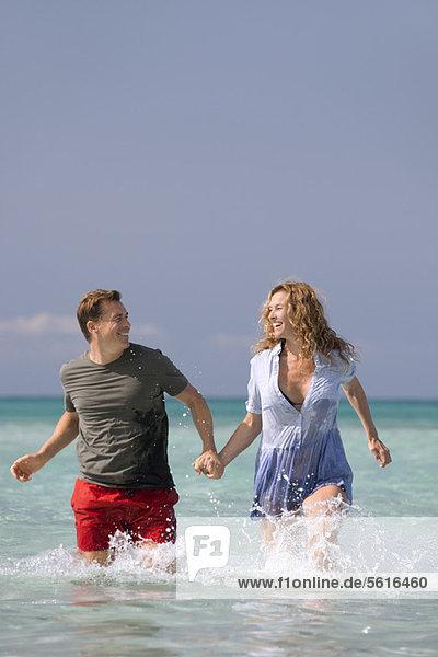 Ein Paar  das im Wasser geht und Händchen hält.