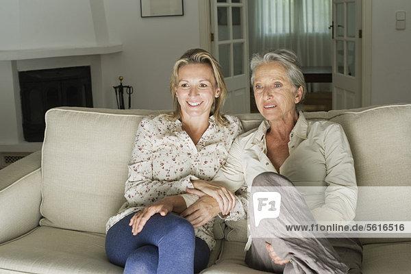 Mutter und Tochter beim Fernsehen im Wohnzimmer