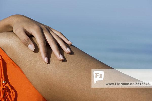 Frau beim Sonnenbaden am Strand  Nahaufnahme der Hand an der Hüfte