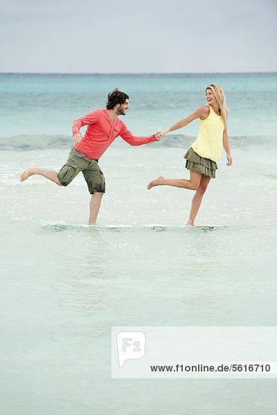 Paar steht auf einem Bein im Wasser am Strand  hält sich an den Händen