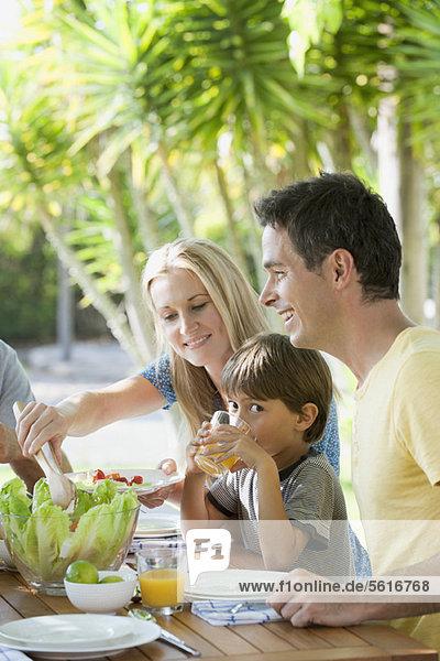 Eltern und junger Sohn beim Frühstück im Freien