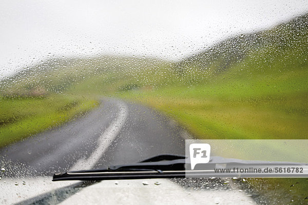 Road and countryside viewed through wet car windshield