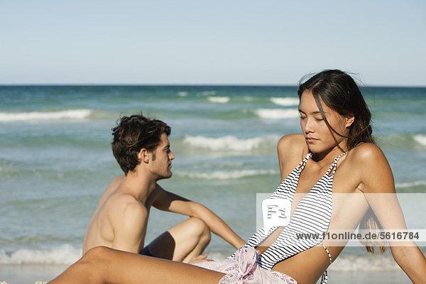 Junge Frau entspannt am Strand mit Freund