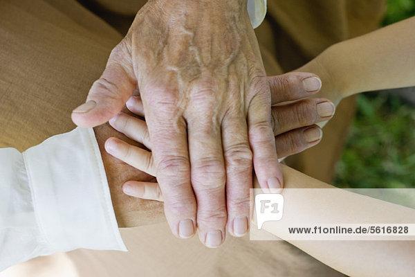 Hände der älteren Frau und des kleinen Mädchens stapelnd