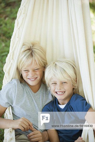 Junge Brüder sitzen zusammen in der Hängematte  Porträt
