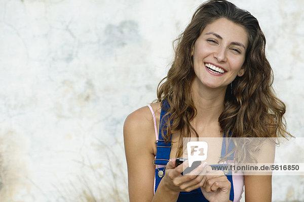 Junge Frau SMS  lächelnd vor der Kamera
