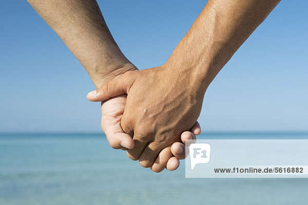 Zwei Männer  die sich an den Händen halten.