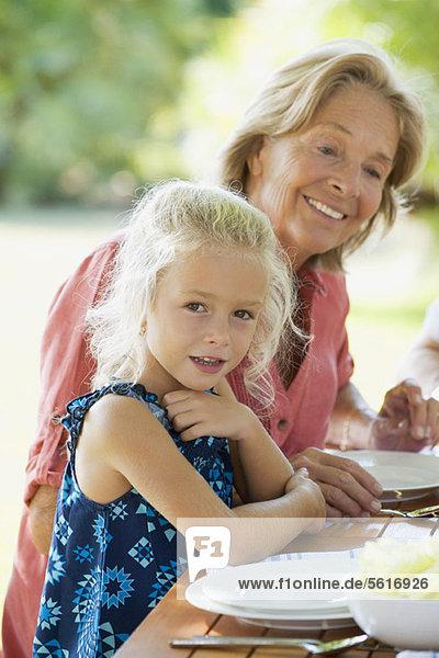 Mädchen beim Essen mit Großmutter im Freien