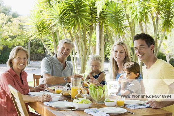 Mehrgenerationen-Familie am Frühstückstisch im Freien  Portrait