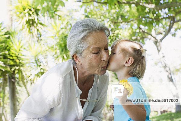 Kleines Mädchen küsst Großmutter auf die Wange