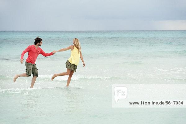Paar läuft Hand in Hand beim Surfen am Strand