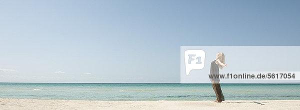 Frau am Strand stehend mit ausgestrecktem Kopf und ausgestreckten Armen