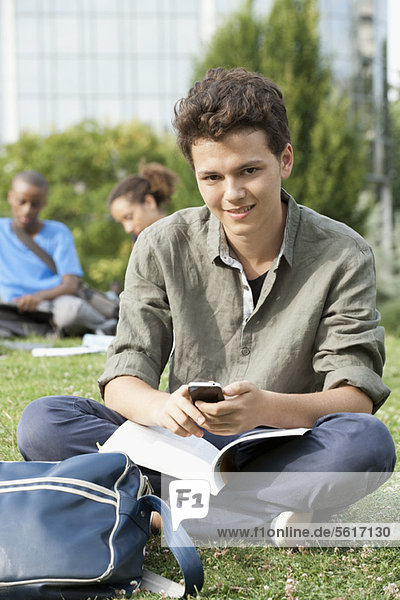 Young man with cell phone  friends in background  portrait