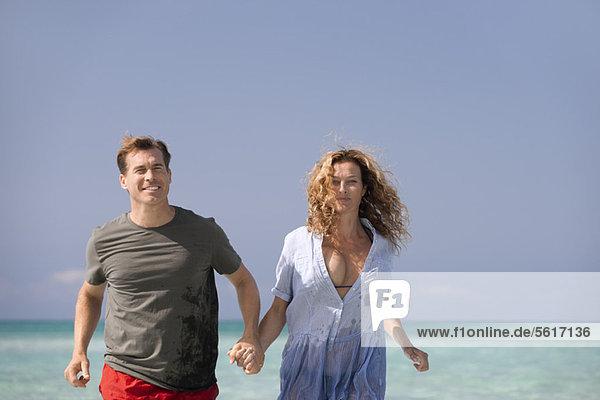 Paar am Strand  Händchen haltend