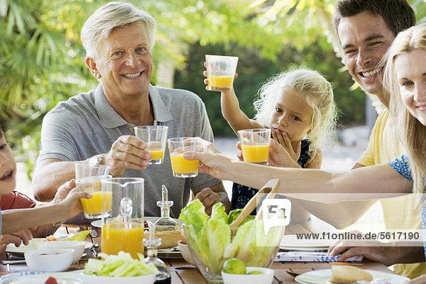 Mehrgenerationen-Familientoast mit Orangensaft im Freien  Portrait