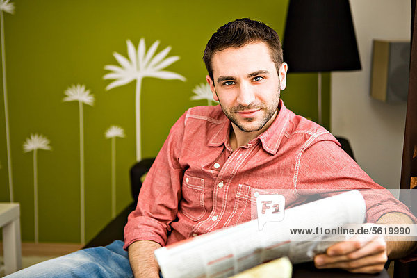 Young man at home  reading a newspaper