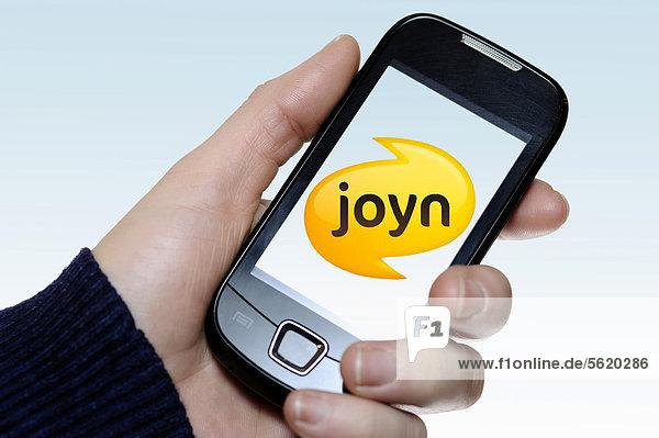 Hand mit Smartphone und Joyn-Logo
