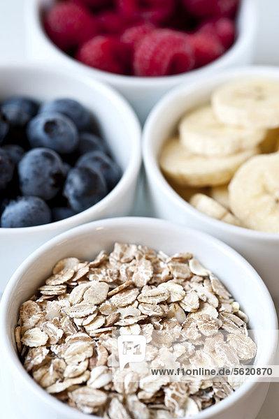Früchte  Bananen  Heidelbeeren  Himbeeren  und Getreideflocken in weißen Schalen Früchte, Bananen, Heidelbeeren, Himbeeren, und Getreideflocken in weißen Schalen