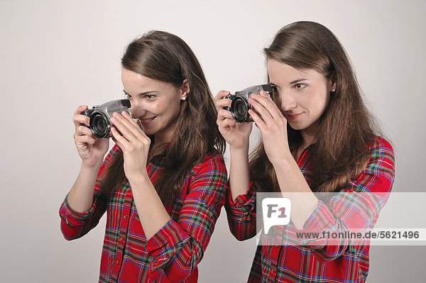 Twin sisters holding digital cameras