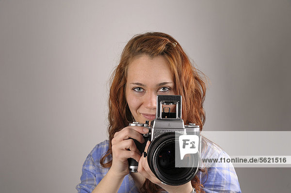 Young woman with red hair taking a photograph with an analog medium format camera Pentacon Six