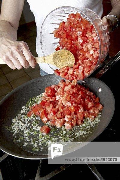 Frau schüttet Tomatenwürfel in Pfanne am Herd