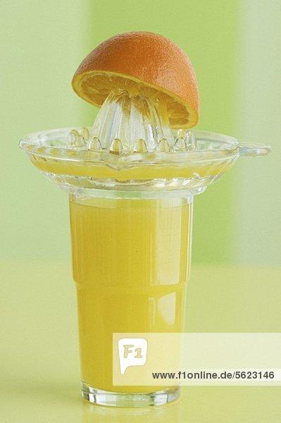 Orangensaft im Glas  Saftpresse und Orangenhälfte