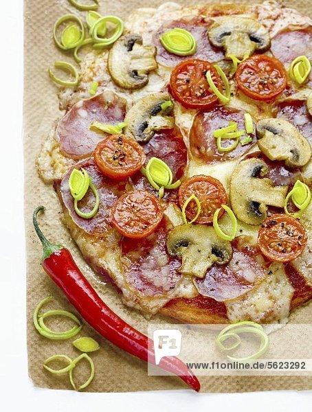 Pizza mit Salami  Champignons  Tomaten  Lauch  Mozzarella und Chilischote