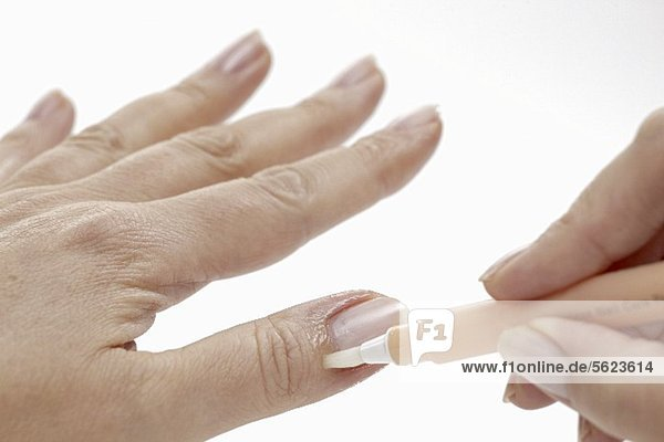 Frau trägt Pflegestift für Nagelbett auf