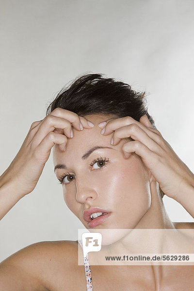 Young woman looking at pimple on her face