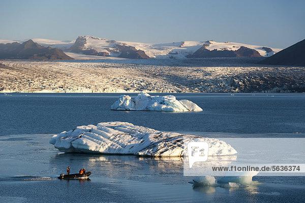 Schlauchboot oder Zodiac Boot  von Asche schwarz gefärbte Eisberge  Gletscherlagune Jökuls·rlÛn  Vatnajökull Gletscher  Austurland  Ost-Island  Island  Europa