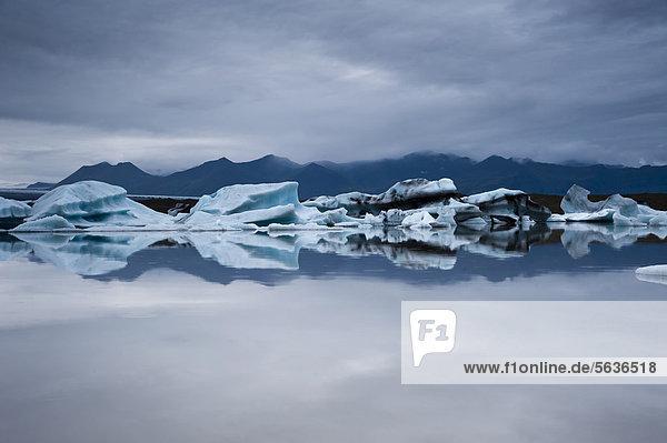 Blaue und von Asche schwarz gefärbte Eisberge  Spiegelung  Gletscherlagune Brei_·rlÛn  Breidarlon  Vatnajökull Gletscher  Austurland  Ost-Island  Island  Europa
