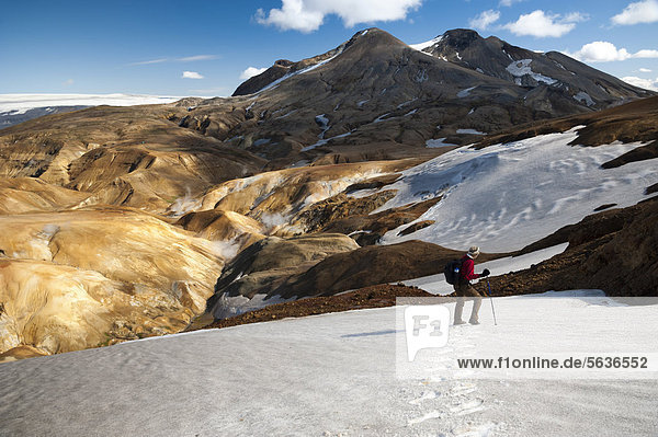 Hiker crossing the snowfield on a trail  snow-capped Rhyolite Mountains  Hveradallir high temperature area  Kerlingarfjoell  highlands  Iceland  Europe