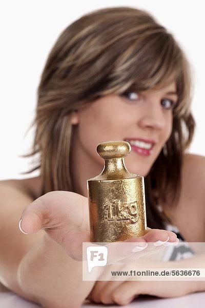 Junge Frau hält ein 1 KG Gewicht in der Hand