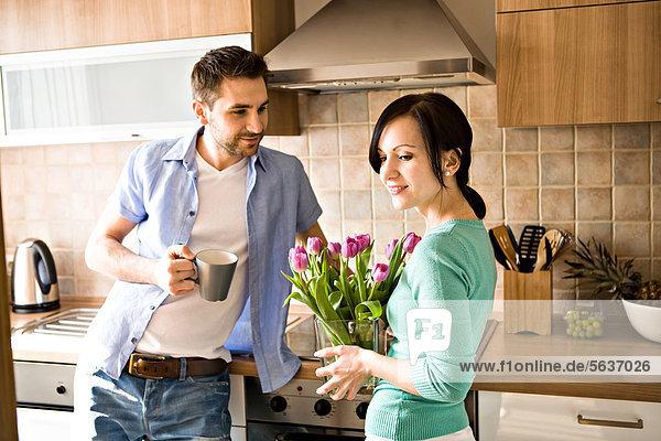Junges Paar mit einem Strauß Tulpen in der Küche