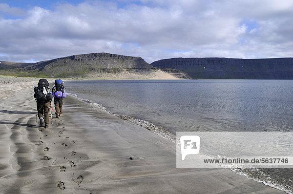 Hikers walking on the beach  A_alvÌk Bay  Adalvik  Hornstrandir  Westfjords  Iceland  Europe