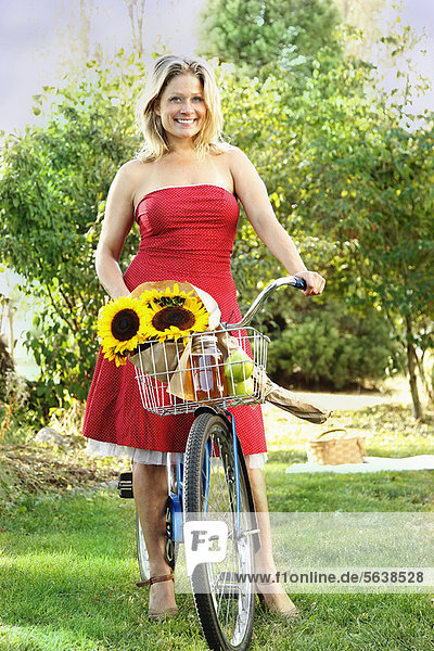 Woman standing with bicycle on grass