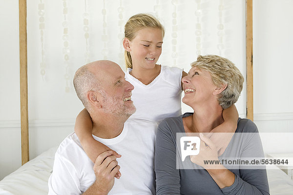 Älteres Paar umarmt Enkelin