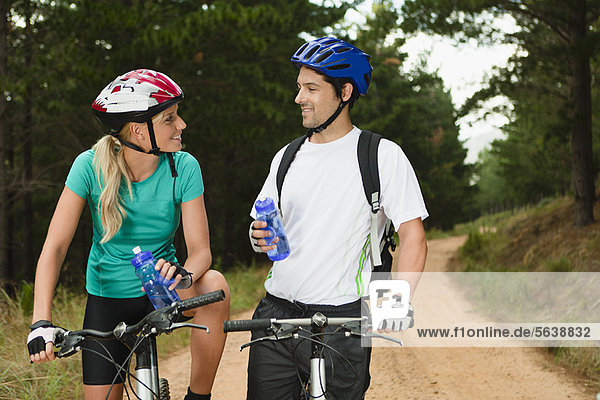 Paar Trinkwasser auf Mountainbikes